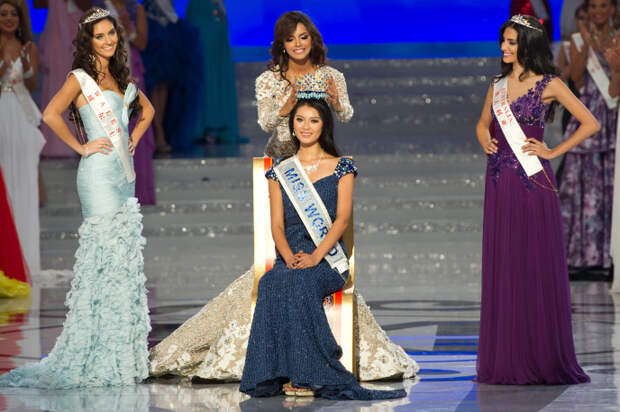 Miss World 2012 winner Yu Wenxia (C) of China receives the crown from previous winner Ivian Sarcos of Venezuela (top C) as second place contestent Miss Wales Sophie Moulds (L) and third place Miss Australia Jessica Kahawaty (R) watch, during the pageant's final ceremony at the Ordos Stadium Arena in the inner Mongolian city of Ordos on August 18, 2012. China's Yu Wenxia of China defeated more than 100 other hopefuls at the glittering ceremony held in the Chinese mining city of Ordos, on the edge of the Gobi desert. AFP PHOTO / Ed Jones