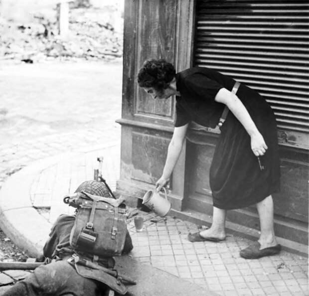 Женщина наливает чай британскому солдату во время уличного боя после высадки союзников в Нормандии в 1944 году.