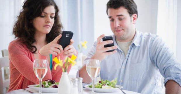 мужчина и женщина с телефоном в руках в ресторане