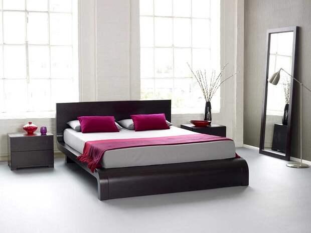 Спальня преображена благодаря размещению оригинальной кровати на платформе плюс ярким малиновым элементам.