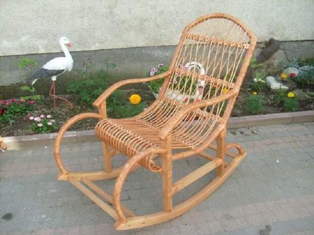 Плетеное из лозы кресло-качалка добавит уюта интерьеру.