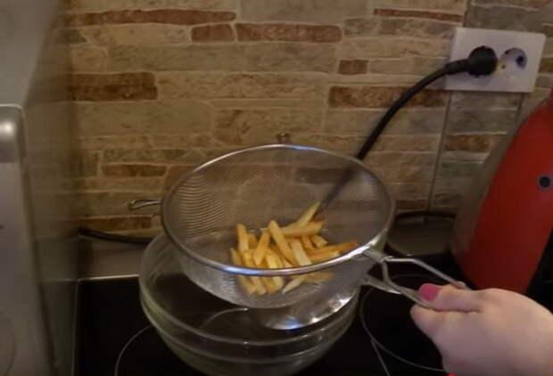 Выкладывайте картофель на дуршлаг, чтобы с него стекло лишнее масло.