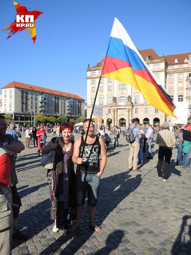 Дарья и немец держат флаг, наполовину немецкий, наполовину русский.