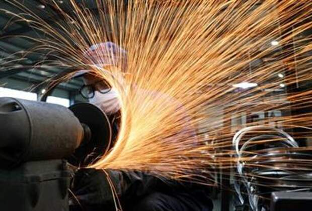 FILE PHOTO: A worker wearing a face mask works on a production line manufacturing bicycle steel rim at a factory in Hangzhou, Zhejiang province, China, March 2, 2020. China Daily via REUTERS