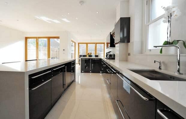 Прекрасный и один из самых лучших вариантов разделения пространства на кухне в темных тонах.