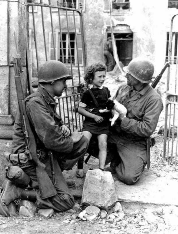 Два американских солдата утешают плачущую девочку, 1944 год.