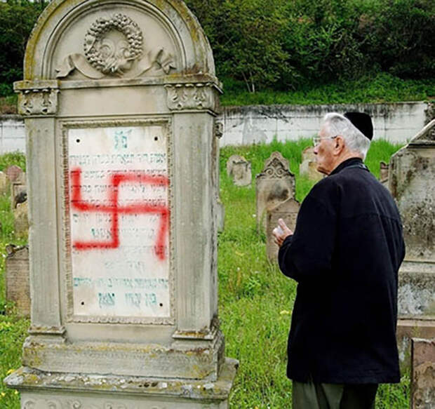 An unidentified member of the Jewish community looks at a swastika painted on a headstone at a Jewish cemetery in Herrlisheim, eastern France, Friday, April 30, 2004. About 100 headstones have been desecrated in the cemetery and the French government quickly condemned the attack. In the past few years, France has suffered a wave of violence against Jewish schools, synagogues and cemeteries that coincided with new fighting in the Middle (AP Photo/Gil Michel)