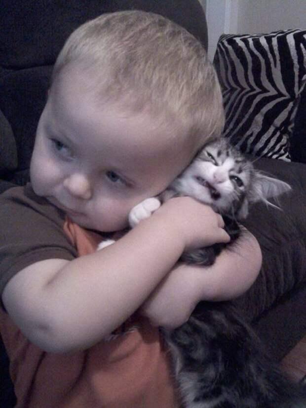 Ребенок тискает кота