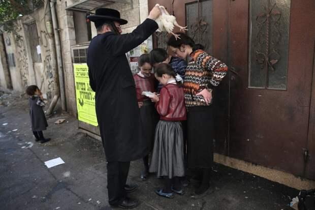 Ультраортодоксальный еврей совершает обряд капарот накануне Йом-Кипурa в квартале Меа Шеарим в Иерусалиме, Израиль.
