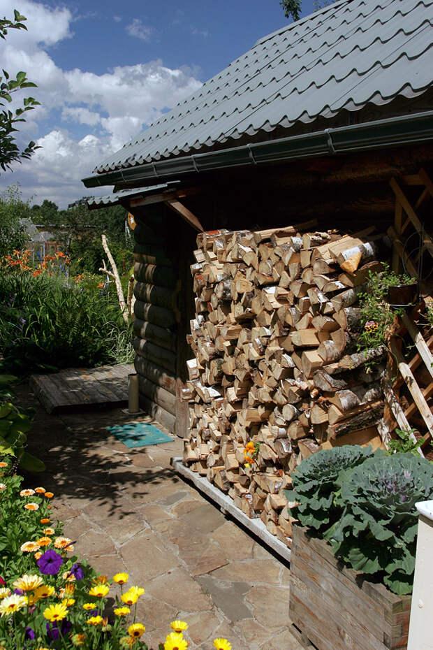 Маскировка старой стены дровами.