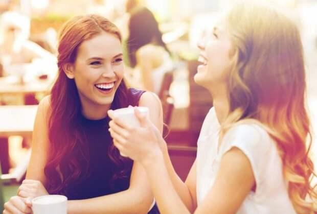 две девушки смеются за столом в кафе