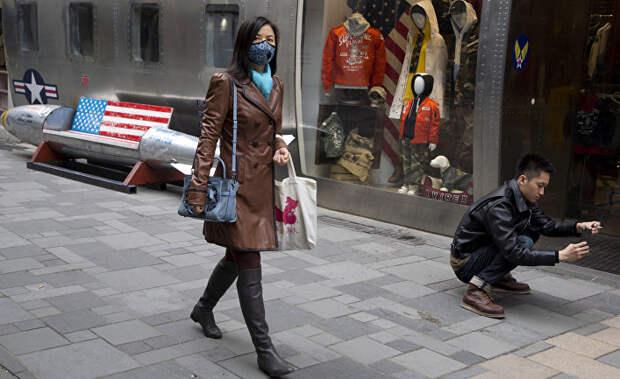 Прохожие возле магазина американских товаров в Пекине, КНР