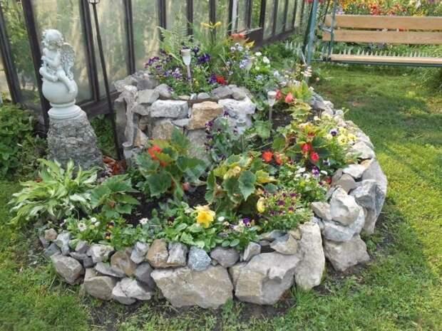 Вот так смотрится готовая клумба из камней с цветами и декором. /Фото: i.pinimg.com