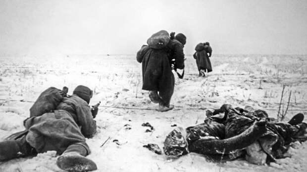 Красноармейцы продвигаются по полю возле окоченевшего тела немецкого солдата под Сталинградом. Фото: © Военный альбом