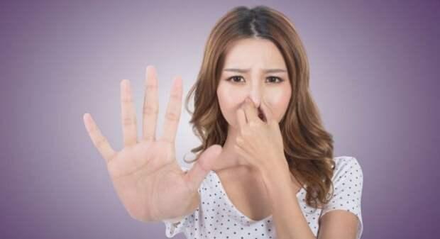 девушка кореянка заткнула нос пальцами