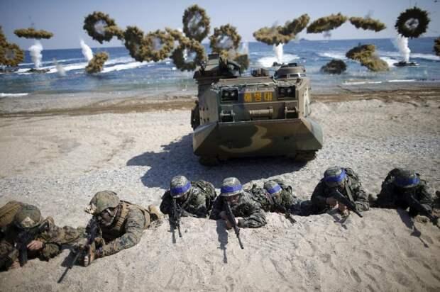 Морские пехотинцы вооруженных сил Южной Кореи (с синими лентами) и США занимают позиции во время совместных учений в Пхохане, Южная Корея, 12 марта 2016 года.