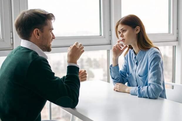 парень и девушка общаются за столом