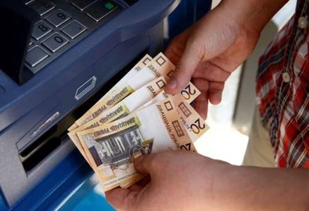 Мужчина снимает деньги в банкомате в Минске, 1 июля 2016 года. REUTERS/Vasily Fedosenko