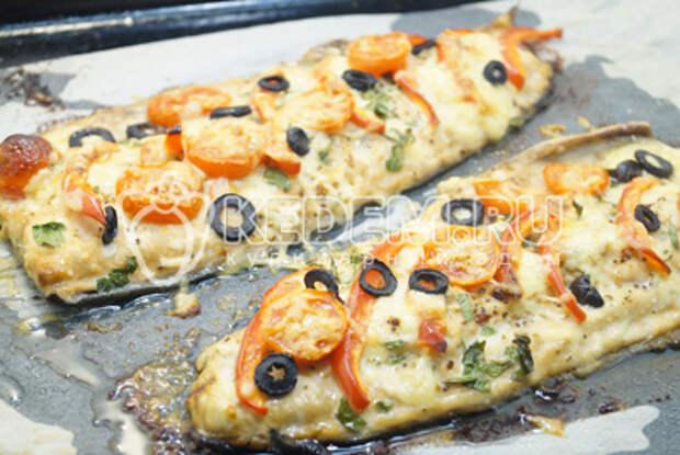 Посыпать тёртым сыром и колечками маслин без косточек.