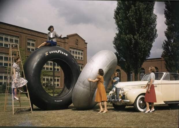 Женщины у огромных резиновых шин, предназначенных для снегового крейсера.