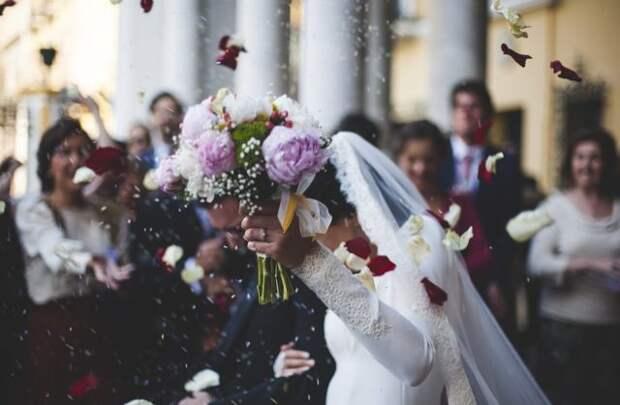 невеста с букетом на фоне гостей