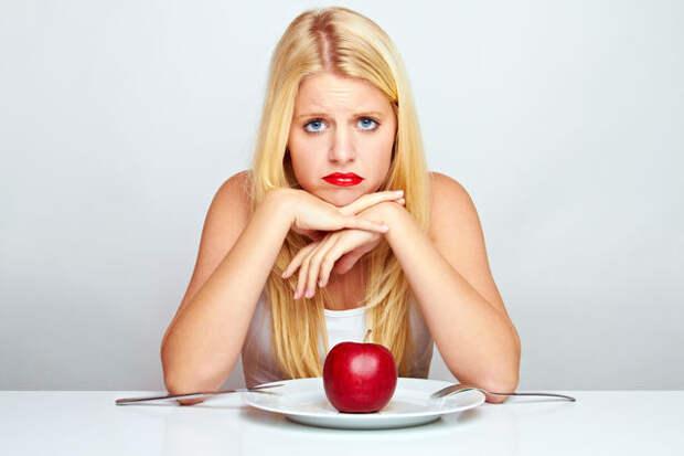 блондинка сидит перед тарелкой с красным яблоком