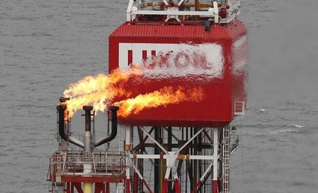A gas torch is seen next to the Lukoil company sign at the Filanovskogo oil platform in the Caspian Sea, Russia October 16, 2018. Picture taken October 16, 2018. REUTERS/Maxim Shemetov