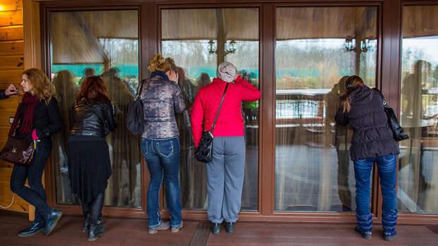 Люди заглядывают в окна оставленной резиденции президента Украины Виктора Януковича...