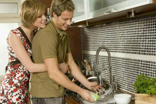 девушка обнимает парня, который моет посуду