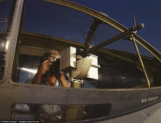 Jesse Rhodes Waller, A.O.M., third class, tries out a 30-caliber machine gun he has just installed in a Navy plane
