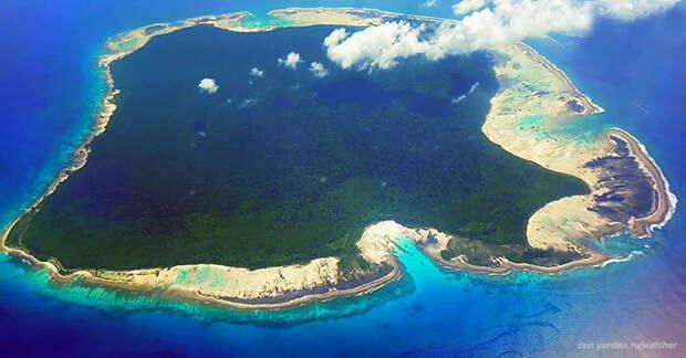 Вокруг Северного Сентинела коралловые рифы. Остров, кроме песчаного берега, покрыт тропическим лесом. Вид с борта самолета.