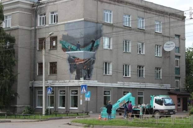 Очень крутое граффити нарисовали в Омке в рамках фестиваля стрит-арта: люди поднимают рояль сквозь провал в полу