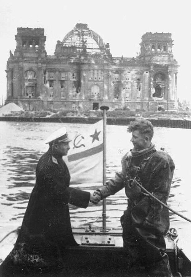 Контр-адмирал советского флота Иванович Крылов благодарит водолаза за расчистку реки Шпрее в центре Берлина  на фоне Рейхстага, в 1945 год