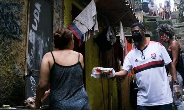 Лидер общины Уильям да Росинья, одетый в защитную маску и перчатки, на этой неделе доставляет пожертвования жителям поселка Росинья в Рио-де-Жанейро.