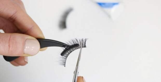 девушка обрезает накладные ресницы