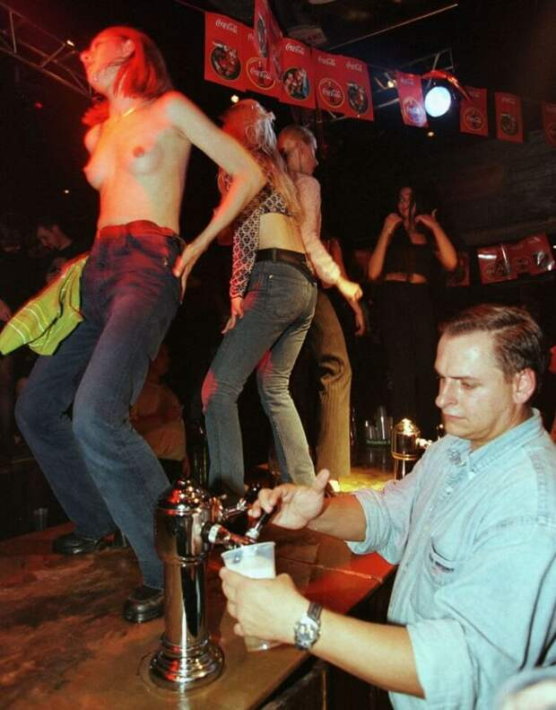 A barman pours a beer while female customers dance on the bar during a ladies' night party at Moscow..