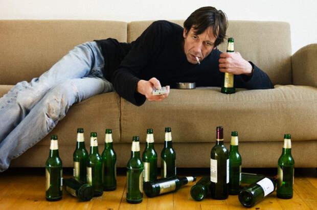 мужчина на диване с пивными бутылками на полу