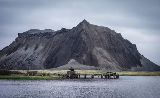 Заброшенный док перед вулканической структурой на острове Атласова, который является частью Курильских островов, Джанель Лугж заброшенные здания, маяк, просторы, россия, церкви