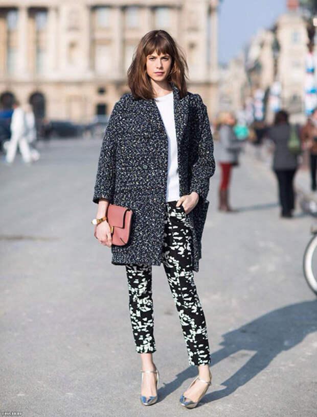 Девушка в брюках с принтом и в темном пальто