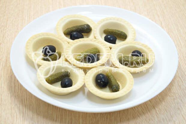 В каждую тарталетку вложить по корнишону и оливке без косточки.