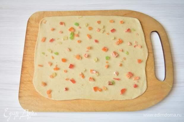 Отдохнувшее тесто раскатать как можно тоньше в пласт. Распределить по всей поверхности теста цукаты, которые предварительно нужно измельчить.