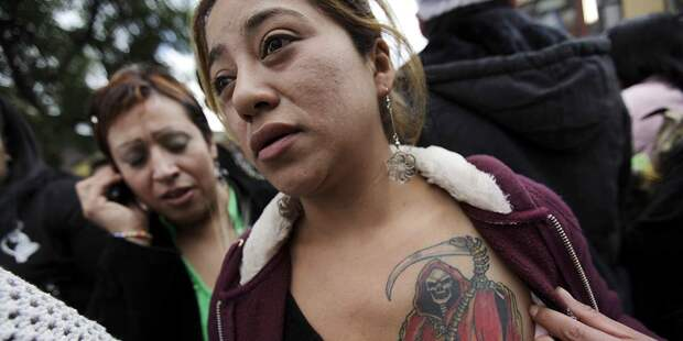 A woman shows her tattoo of La Santa Muerte (The Saint of Death) near her altar in Tepito in Mexico City