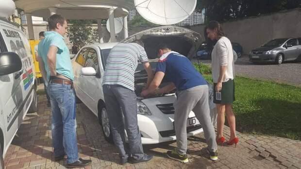 вполне нормальная ситуация. мужчины помогают женщине с автомобилем