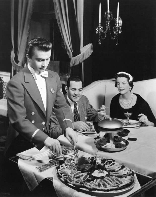Официант подает мини хот-доги в отеле - Ambassador East Hotel в Чикаго, США. 12 апреля 1955 года. история, ретро, фото