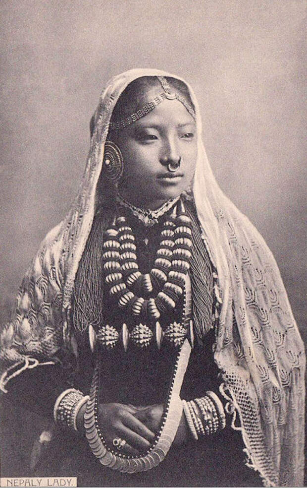В национальном костюме и традиционных для своей народности украшениях.