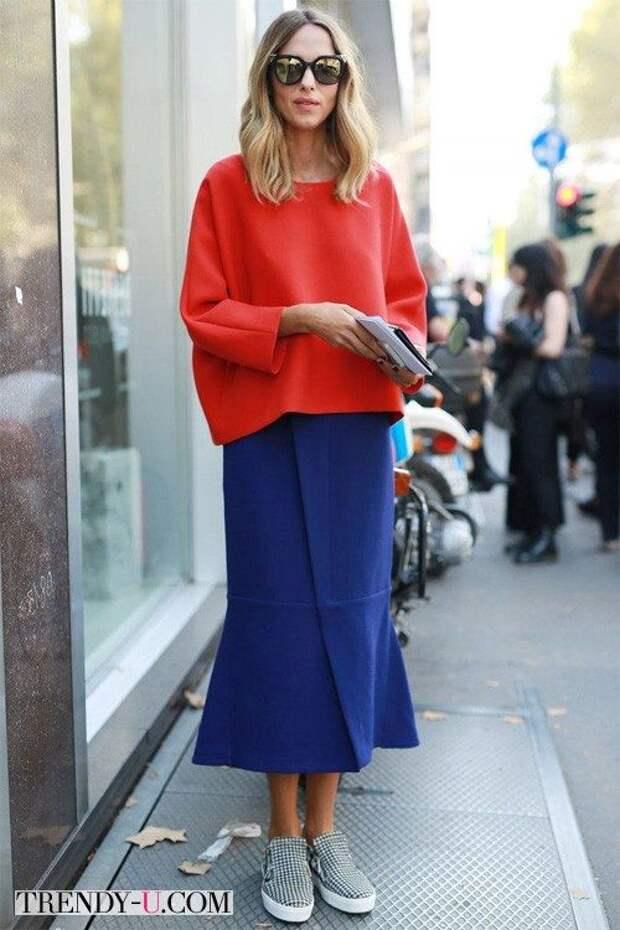 Модница в красном объемном топе, синей юбке гаде и слипонах