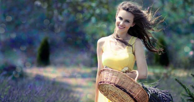 Девушка в жёлтом платье идёт по полю с корзиной цветов