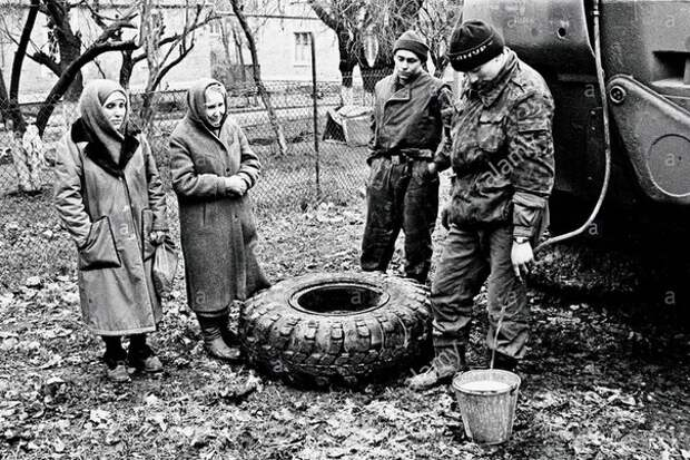 Морские пехотинцы ВС России (рота обеспечения) делятся питьевой водой с мирными жителями Грозного. Февраль 1995 года