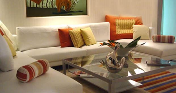 Фото гостинной со стеклянным столом, разноцветным ковром и картиной