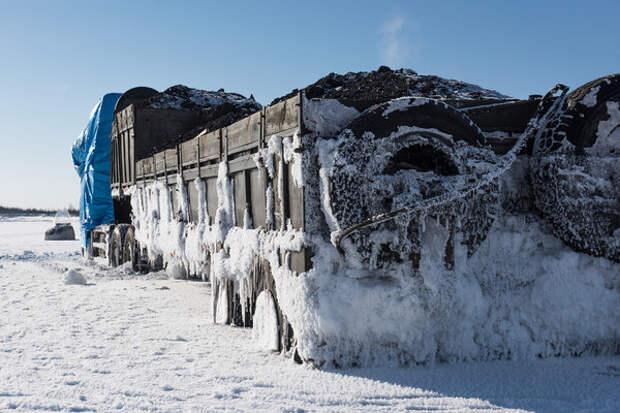 """Машина, попавшая в ледяной плен. Ваня рассказывает: """"Хозяин уже не один месяц живет около нее. Транспортное средство – единственный кормилец. Если не успеть вытащить до наступления тепла, то лед просто напросто переломит грузовик""""."""